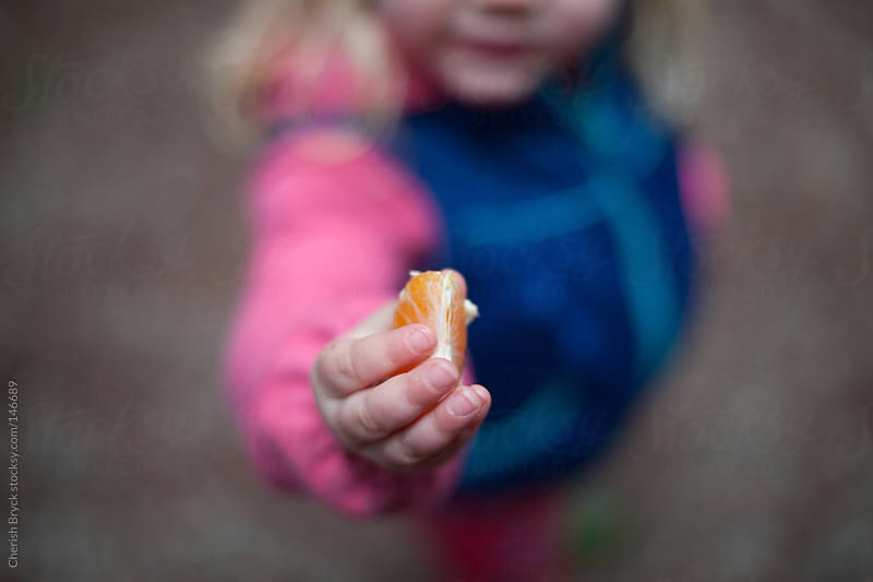 Child offers orange in her hand. by Cherish Bryck for Stocksy United