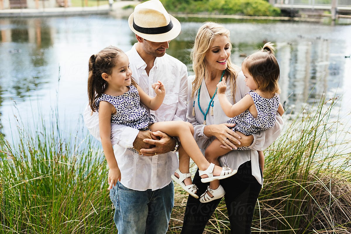 Young Family Standing By Lake Happily With Their Two Young Daughters. by  Image Supply Co - Family, Lifestyle