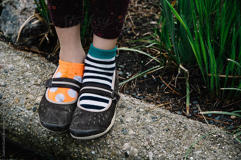 A girl's feet with shoes and unmatched pair of socks by Gabriel (Gabi) Bucataru for Stocksy United