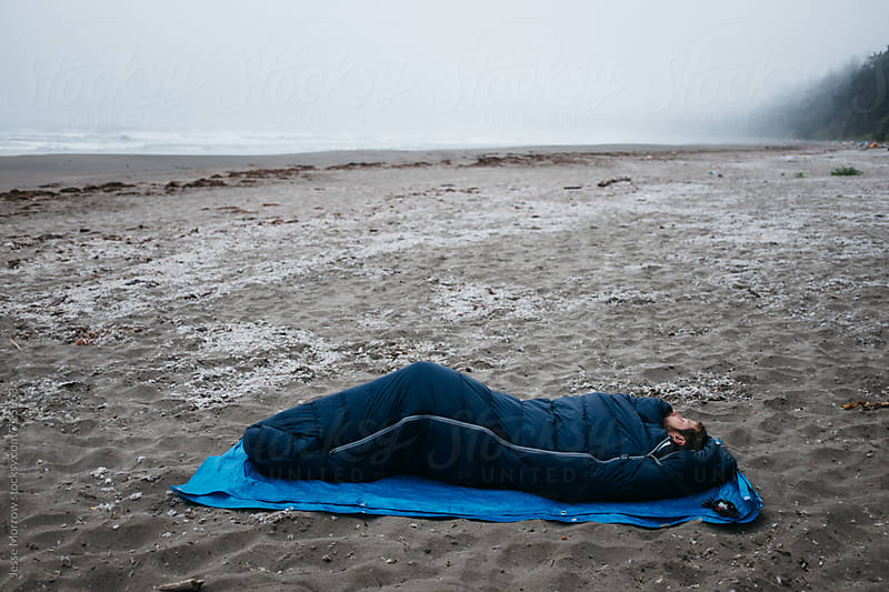 young male sleeping alone on beach in sleeping bag by Jesse Morrow for Stocksy United
