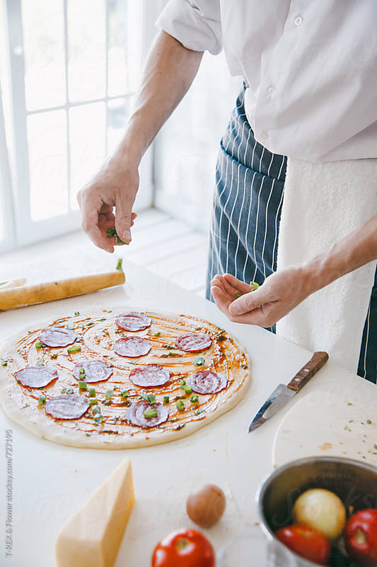 Pizza chef puts salami on round dough by Danil Nevsky for Stocksy United