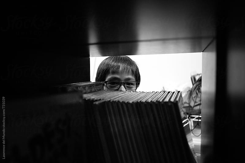 Young boy with glasses peering through a bookshelf with books inside a library by Lawrence del Mundo for Stocksy United