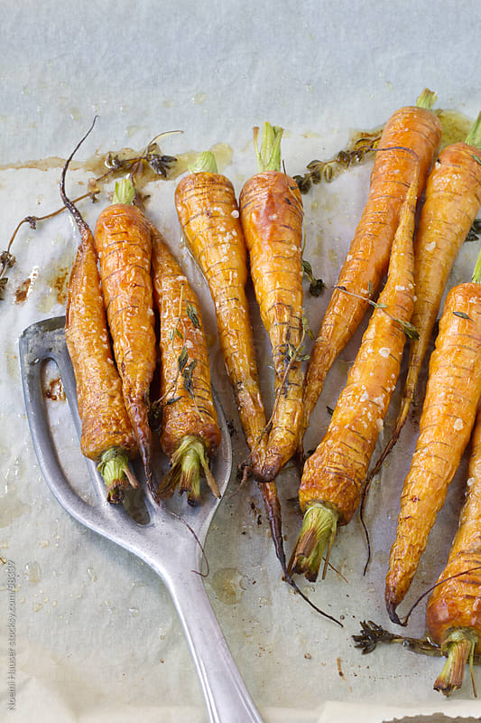 Oven roasted carrots with slotted spatula on baking paper by Noemi Hauser for Stocksy United