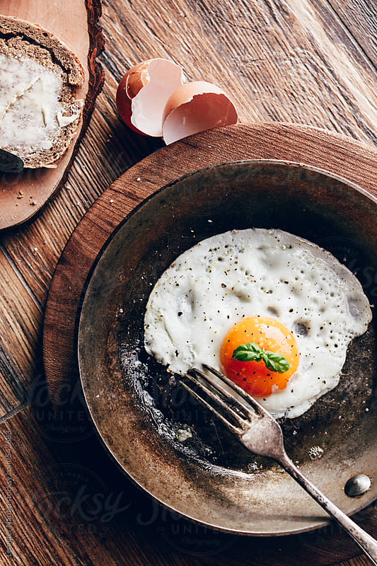 fried egg in griddle, bread and butter on wooden background by Leander Nardin for Stocksy United