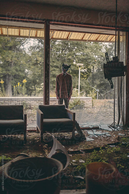 Creepy Abandoned Resort Man With mask by Jake Elko for Stocksy United
