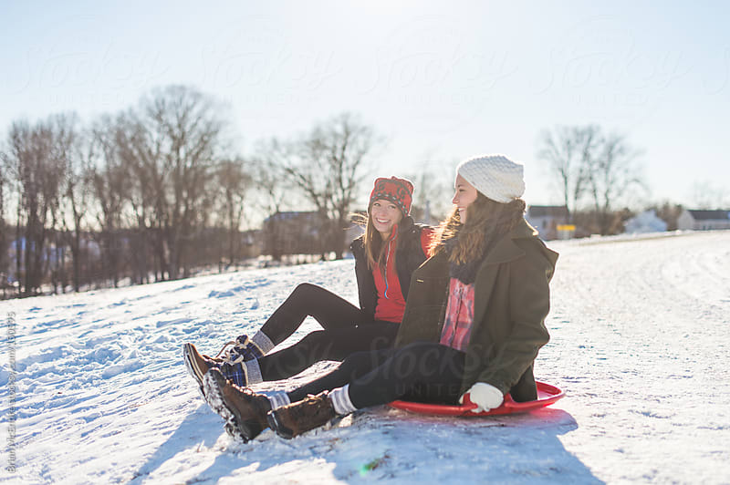 Girl friends chat while sitting on sleds on a cold winter day by Brian McEntire for Stocksy United