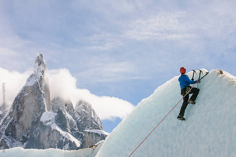 Man climbing on ice wall on a glacier in Patagonia with Cerro Torre on background by Alejandro Moreno de Carlos for Stocksy United