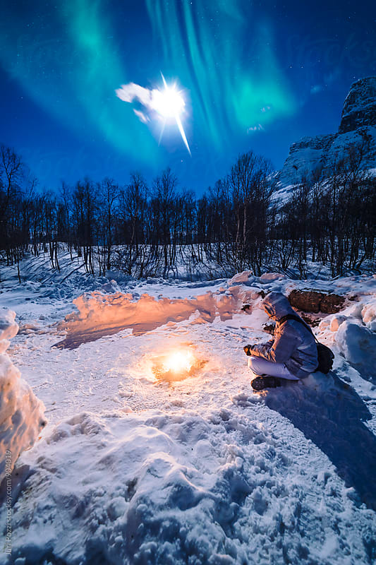 man sitting next to a campfire at night below northern lights by Juri Pozzi for Stocksy United