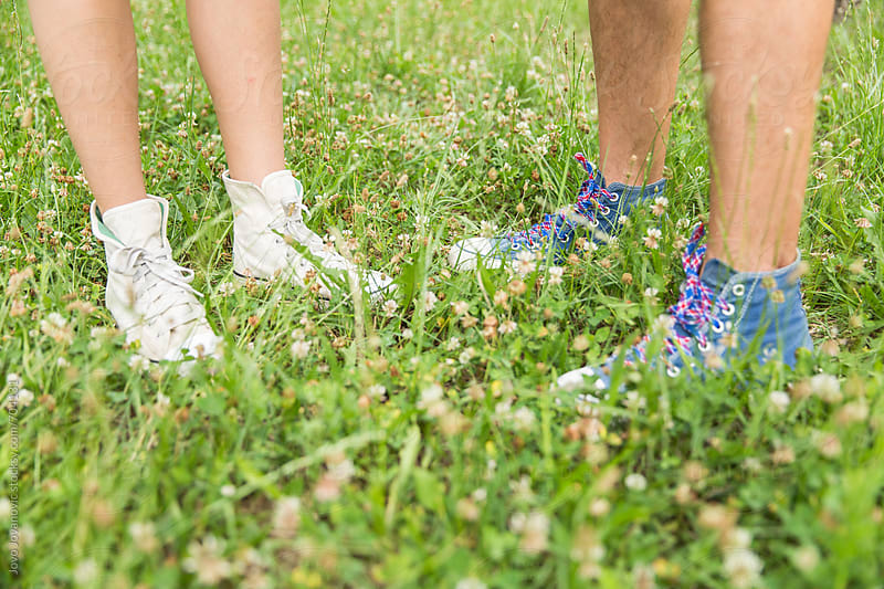 Couple wearing sneakers and standing in green grass by Jovo Jovanovic for Stocksy United