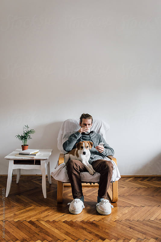 Man sitting and drinking a coffee at living room by Kate & Mary for Stocksy United