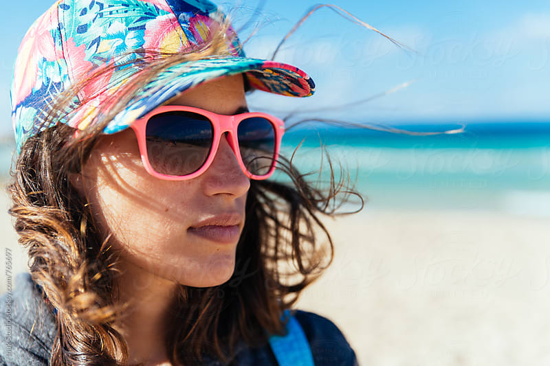 Stylish young woman portrait wearing pink sunglasses and a colourful cap on a windy day in the beach by Inuk Studio for Stocksy United