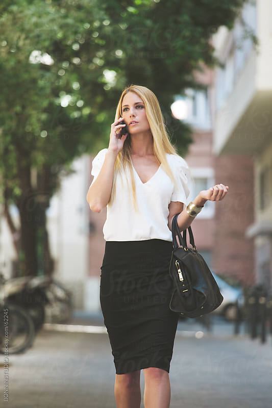 Young businesswoman taking with smartphone on the street. by BONNINSTUDIO for Stocksy United