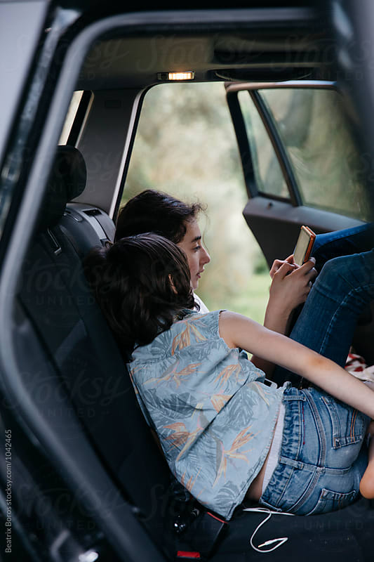 Boy watching his sister using a tablet while waiting in the car by Beatrix Boros for Stocksy United