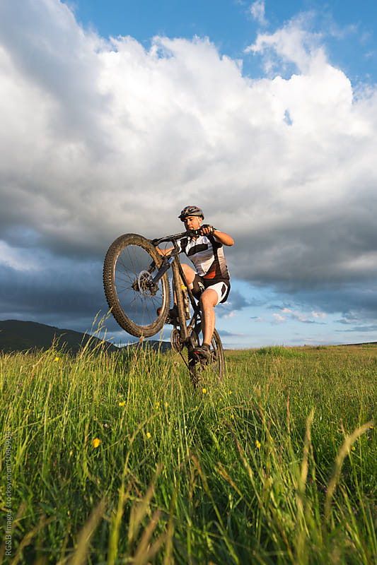 Man riding mountain bike on one wheel in tall grass  by RG&B Images for Stocksy United