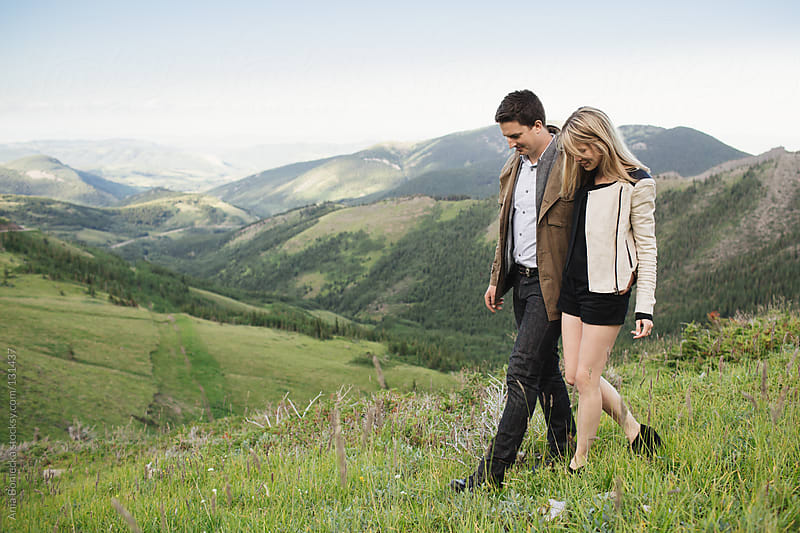 A young couple walking together through a mountain valley by Ania Boniecka for Stocksy United
