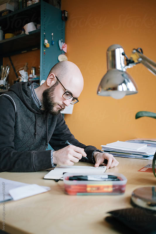 A designer sketching behind his desk at his home office by Ivo de Bruijn for Stocksy United