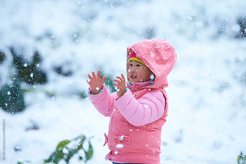 one little asian girl in snow by Bo Bo for Stocksy United