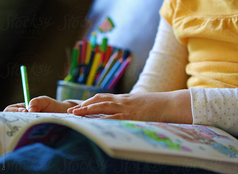 Little girl coloring in her book by Carolyn Lagattuta for Stocksy United