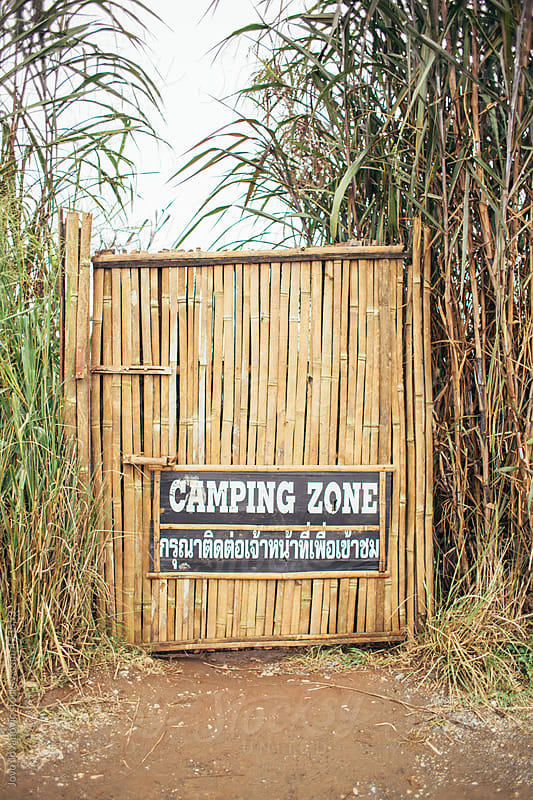 Bamboo door with camping zone sign in jungle by Jovo Jovanovic for Stocksy United