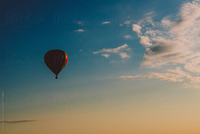 Hot air balloon during sunrise by Lauren Naefe for Stocksy United
