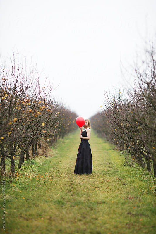 Girl with a balloon standing in orchard by Jovana Rikalo for Stocksy United