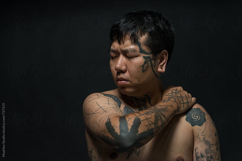 Portrait of young man with tattooed upper body by MaaHoo Studio for Stocksy United