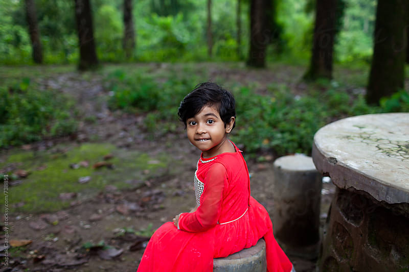 Little girl looking at camera and making faces in a forest by Saptak Ganguly for Stocksy United