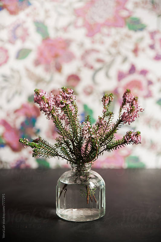 Flowers in small bottle, in front of a floral background by Vera Lair for Stocksy United