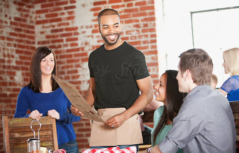 Barbeque: Waiter Seating Guest at Table by Sean Locke for Stocksy United