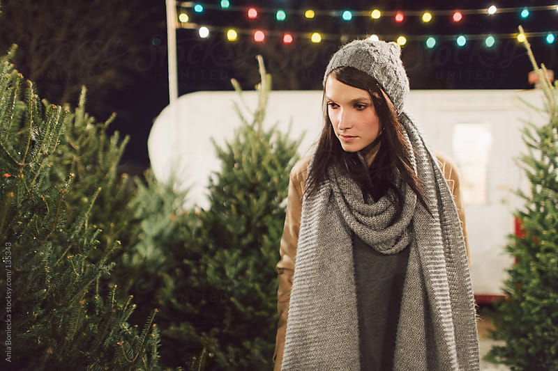 A woman looking at christmas trees  by Ania Boniecka for Stocksy United