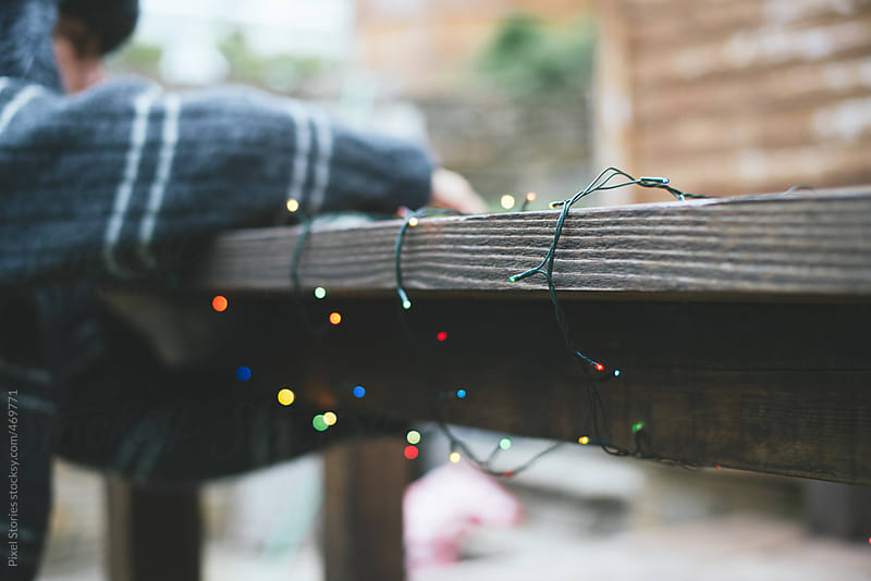 Person decorating front porch with Christmas lights by Pixel Stories for Stocksy United