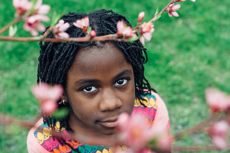 African American girl among peach tree bloom by Gabriel (Gabi) Bucataru for Stocksy United