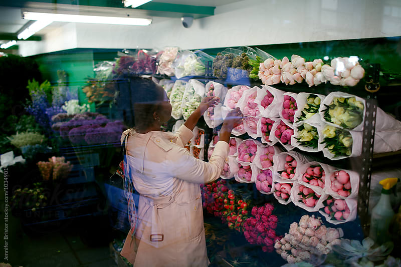 Woman shopping for flowers in flower shop by Jennifer Brister for Stocksy United
