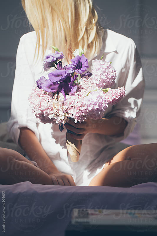 Woman With a Lilac Bouquet Sitting on Bed by Lumina for Stocksy United