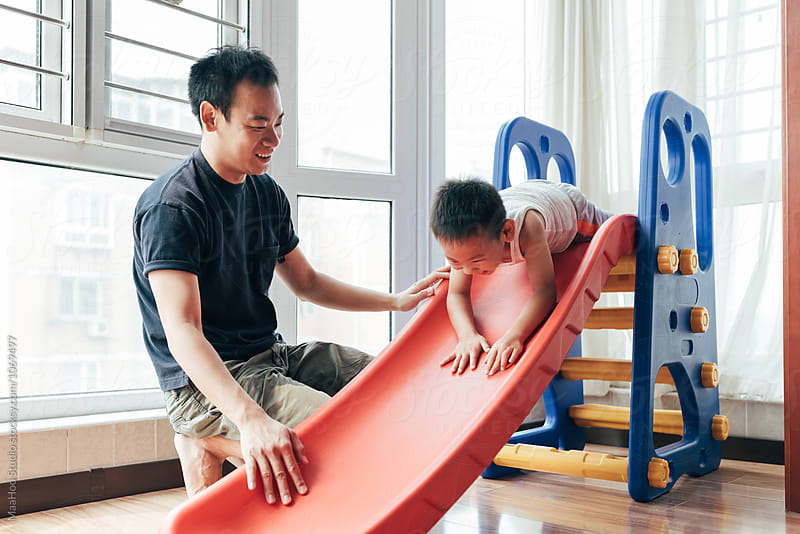 Father and son playing slide at home by Maa Hoo for Stocksy United