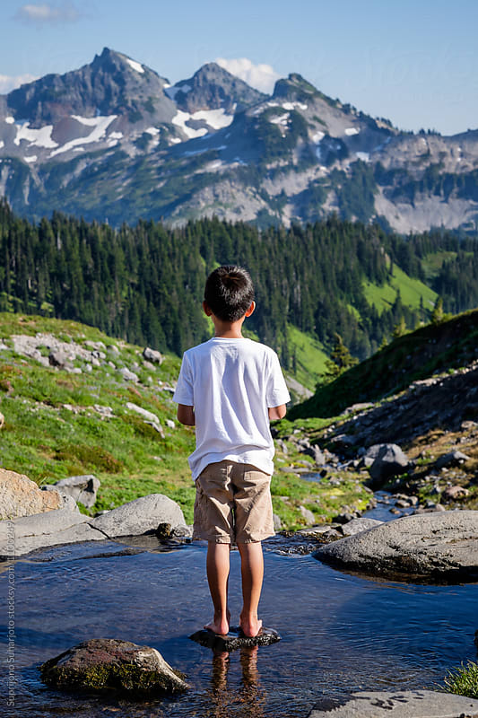Young boy outdoor enjoying the view of the beautiful mountain sc by Suprijono Suharjoto for Stocksy United