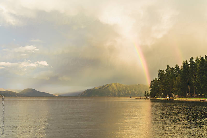 View on rainbow over lake by Trent Lanz for Stocksy United