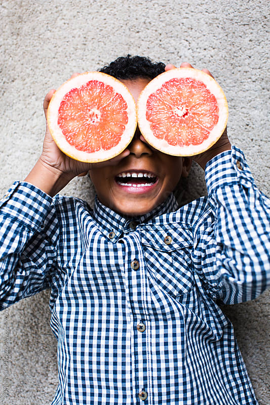 Funny kid playing with an orange.  by BONNINSTUDIO for Stocksy United