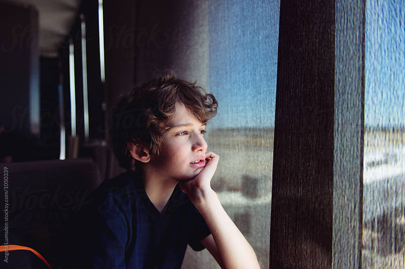 Teenage boy looks through the blinds of a large shaded window at an airport by Angela Lumsden for Stocksy United