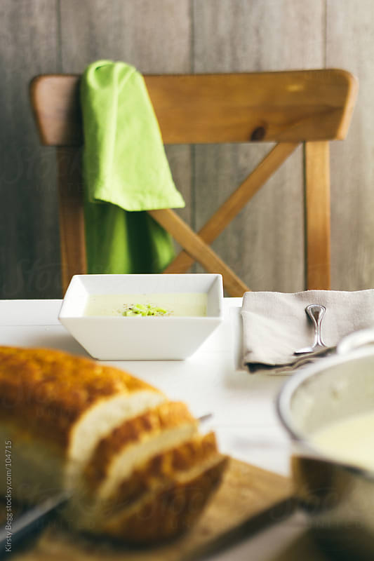 Leek and potato soup and bread set out by Kirsty Begg for Stocksy United
