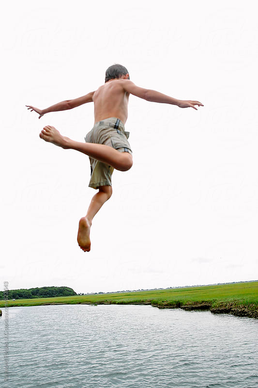 Boy Jumping off Dock Cape Cod, Massachusetts by Raymond Forbes LLC for Stocksy United