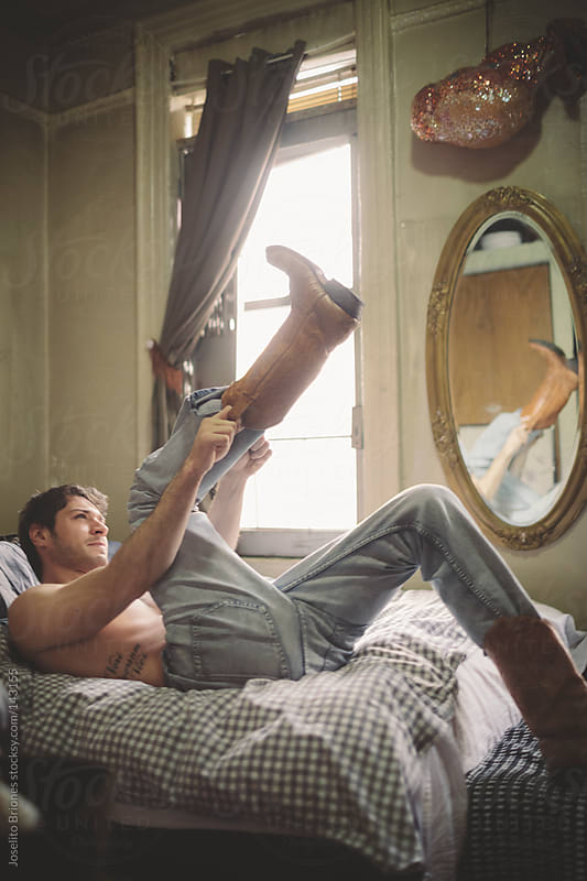Shirtless Man in Jeans Struggling to Put Boots on in Bed by Joselito Briones for Stocksy United