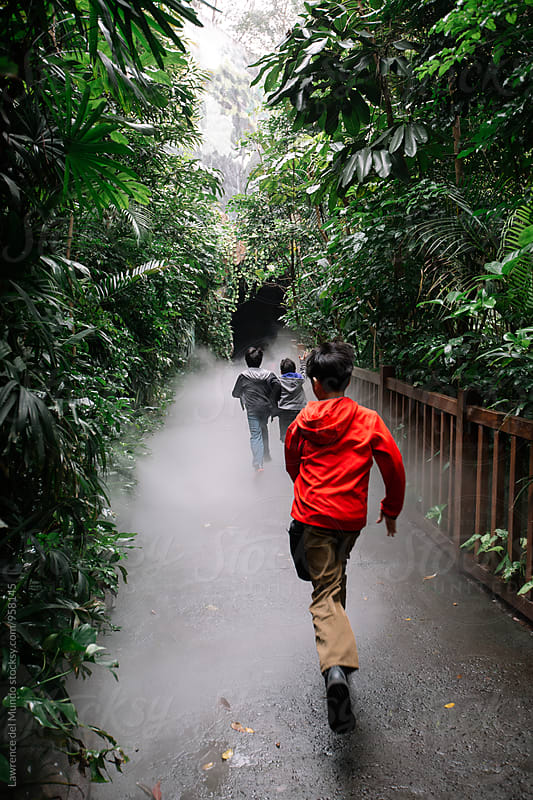 Boys running through a foggy pathway and toward a tunnel  by Lawrence del Mundo for Stocksy United