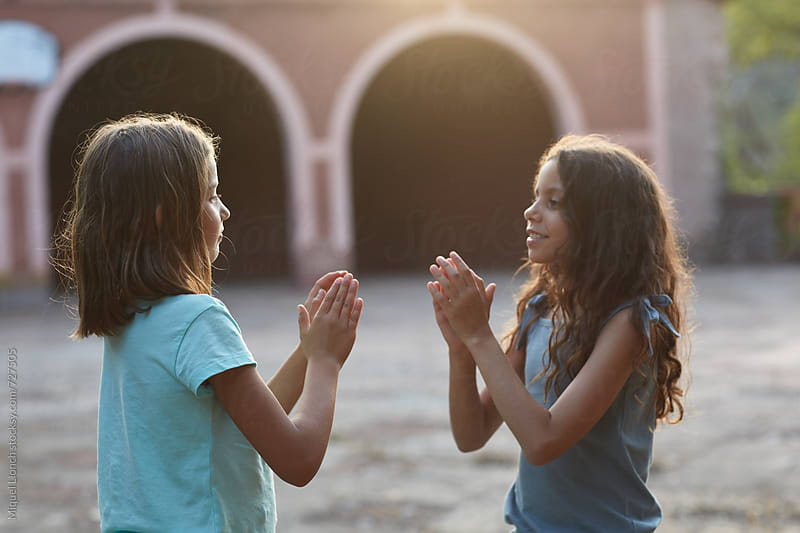 Two little girls playing together a hands game at sunset by Miquel Llonch for Stocksy United