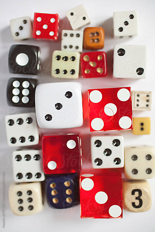 a collection of vintage dice arranged on a white background by Natalie JEFFCOTT for Stocksy United