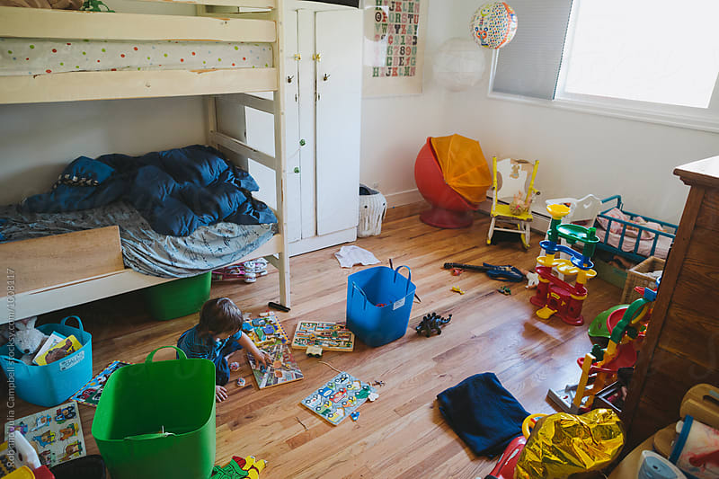Toddler playing in messy room