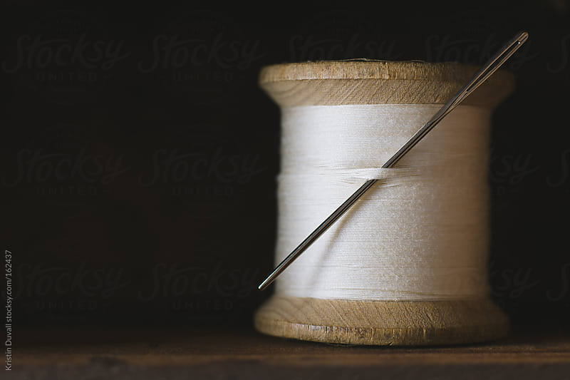 Spool of white cotton thread with needle by Kristin Duvall for Stocksy United