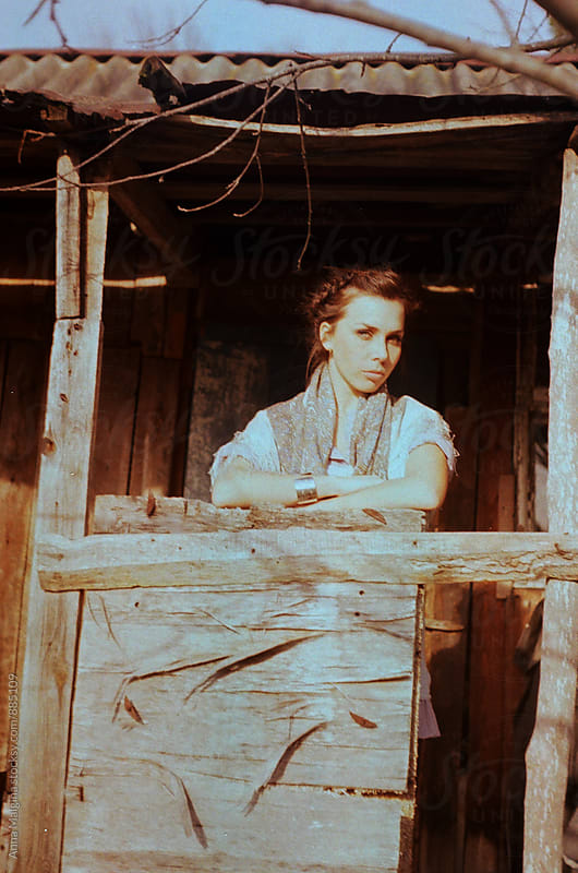 A film portrait of a young beautiful woman standing on a rustic cabin porch. by Anna Malgina for Stocksy United