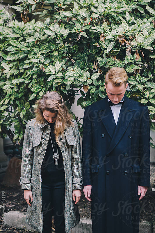Young couple standing side by side in front of foliage by kkgas for Stocksy United