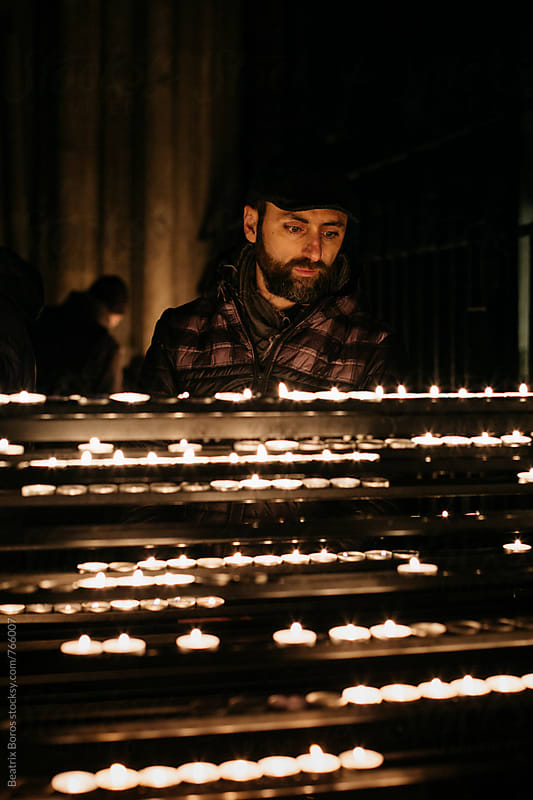 Man in a chrurch behind rows of candles by Beatrix Boros for Stocksy United